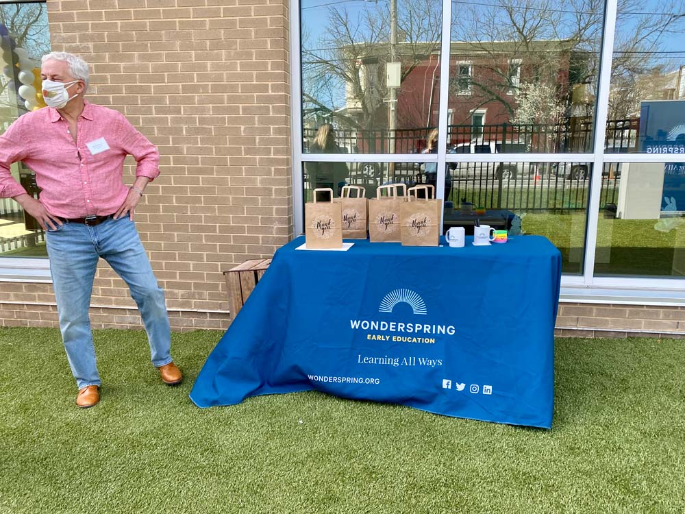 Man in pink shirt standing next to blue table set up outside infront of building