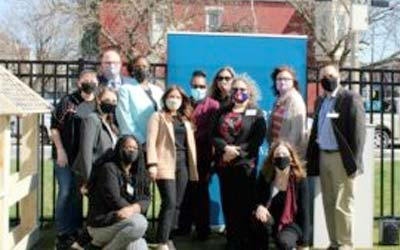 People wearing masks posing for photo outside
